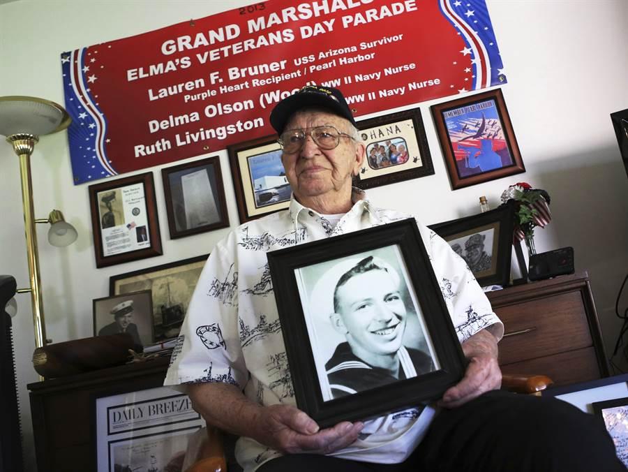 珍珠港老兵布鲁纳,拿着自己年轻时的照片.jpg